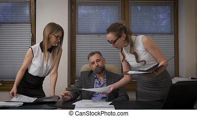 Two women assistants to apply for signature to his boss. A respectable businessman with gray hair is in its solid cabinet.