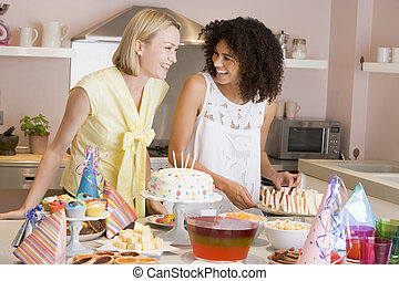 Two women at party getting sandwiches smiling