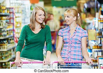 two women at supermarket shopping