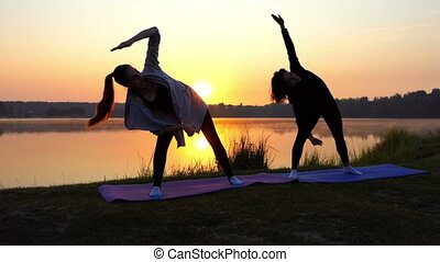 Two Women Bend Right And Left, While Raising Their Hands at Sunset in Slo-Mo