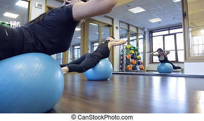 Two women black sportswear do exercises on fitball in gym.