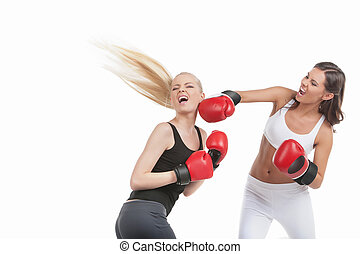 Two women boxing. Two young women boxing while isolated on white