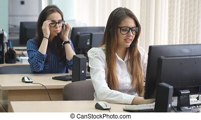 Two women call center use computer