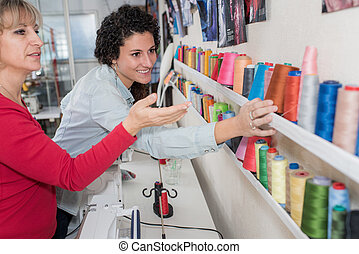 two women choosing thread reels in sewing store