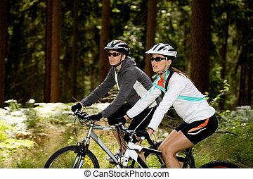 two women riding bikes through the forest
