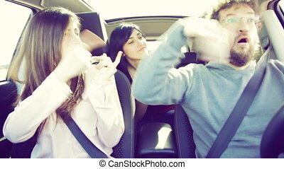 Two women dancing in car with man