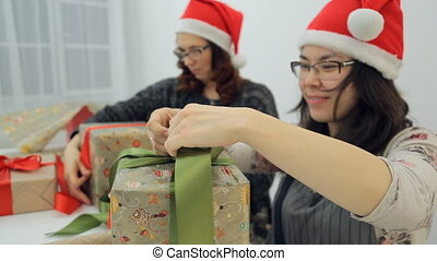Two women decorate gifts with bows for Christmas, New Year.