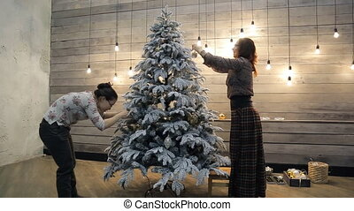 Two women decorating Christmas tree with smiling and talking.