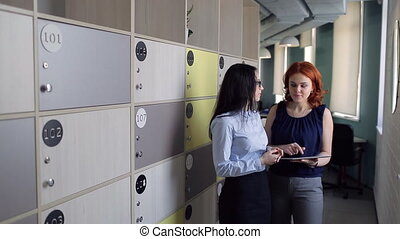 Two women discuss something in office near storage cells....