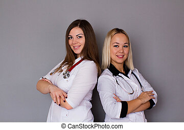 Two women doctor in white medical coats on a gray background. Healthcare concept