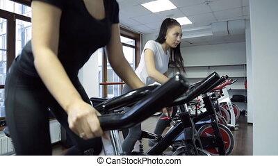 Two women doing exercise on stationary bike in fitness studio