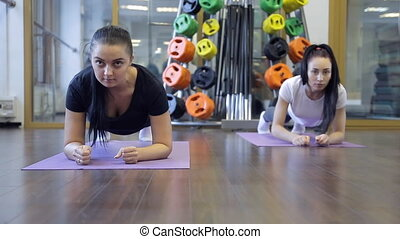 Two women doing exercise strap on his elbows in the sport class.