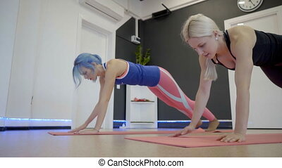 Two women doing plank exercise on floor in sports club.