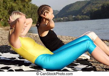 sit-ups outdoor - two women doing sit-ups outdoor