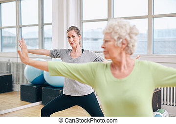 Two women doing stretching and aerobics workout