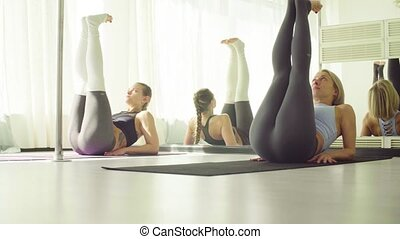 Two women doing warm-up gymnastic exercises for the abdomen.