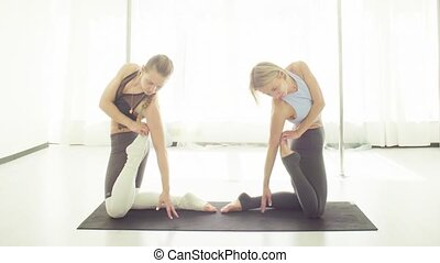Two women doing yoga asanas in studio.