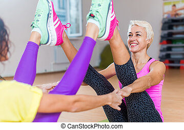 Two women doing yoga buddy boat pose sitting on mats with straight legs and feet upwards holding their hands indoors in a gym