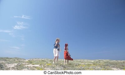 two women dressed in boho style with a dog walking along the beach