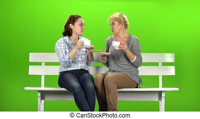 Two women drink tea and talk. Green screen
