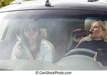 Two women drinking while driving a car - Two attractive...