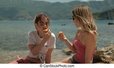 Two women eat fruit and communicate on a sunny beach.