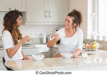 Two women eating bowls of cereal in kitchen
