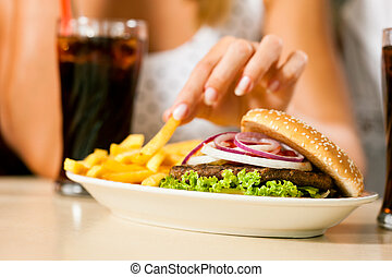 Two women eating hamburger and drinking soda - A woman...