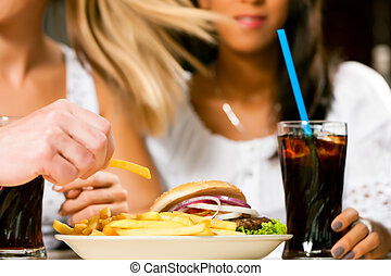 Two women eating hamburger and drinking soda - Two women -...
