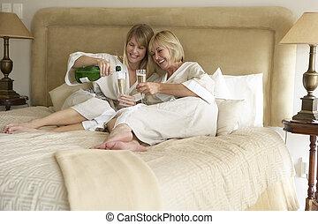 Two Women Enjoying Champagne In Bedroom