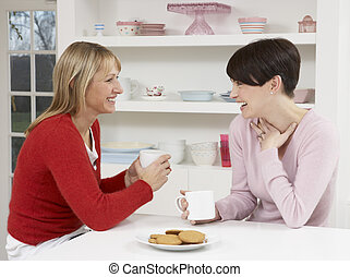 Two Women Enjoying Hot Drink In Kitchen