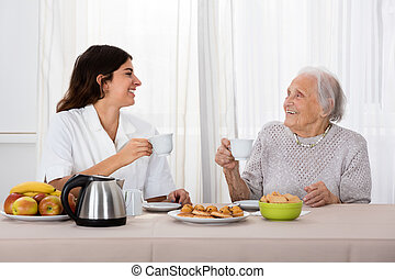 Two Women Enjoying Tea And Cookies