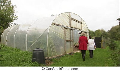 Two women entering a greenhouse - A moving shot of two women...