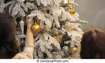 Two women examine Christmas tree, correct branches. View...