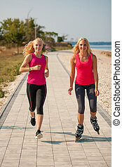 Two women exercise on beach running and rollerblade skating near sea