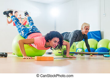 Two women exercising with stability balls doing push-ups in a gym class