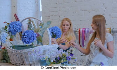 Two women florists making large floral basket with flowers...