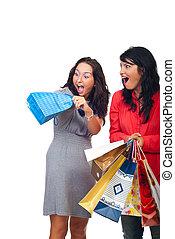 Two women friends having fun with a bag