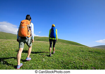 two women friends hiking in grassland mountains top