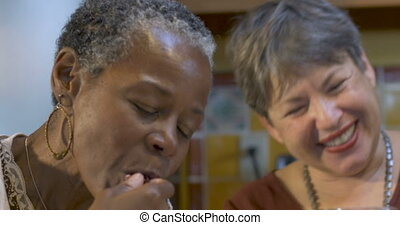 Two women friends over 60 eating, drinking and laughing together at a party