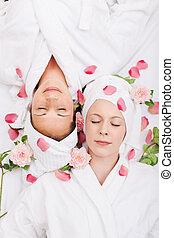 Two women friends relaxing in a spa lying head to head on...