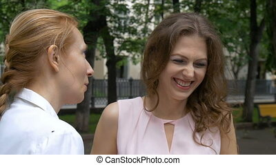 Two women friends talk in the park. A beautiful summer sunny day. close-up