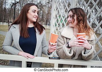 two women girlfriends drink coffee in the park and have fun