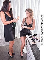 two women having a bottle of champagne
