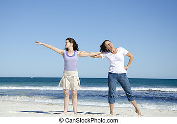 Two women having fun at the beach - Mother and daughter, two...