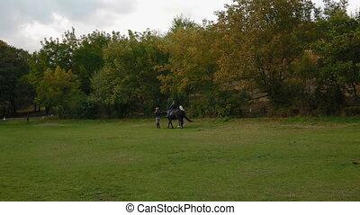 Two women help little boy to ride a horse
