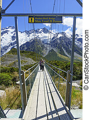 Two women hikers cross walkers Hooker Bluff Bridge bridge over river with Southern Alps background