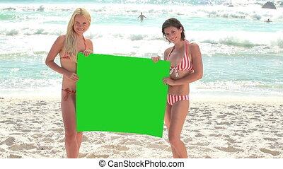 Two women holding a green screen