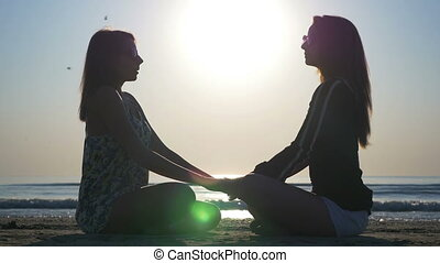 Two women holding hands doing breathe exercises on the beach