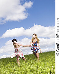 Two women holding hands on a field